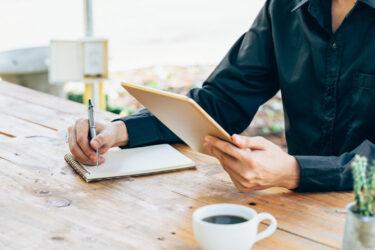 Man zit achter bureau en heeft een tablet in zijn handen. Hij schrijft op een notitieblok.